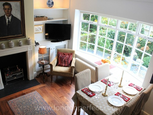 The charming living room with large window overlooking private entrance garden