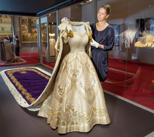 Exhibition curator Caroline de Guitaut adds the finishing touches to the display of The Queen's Coronation Dress and Robe. Photo from the Royal Collection.