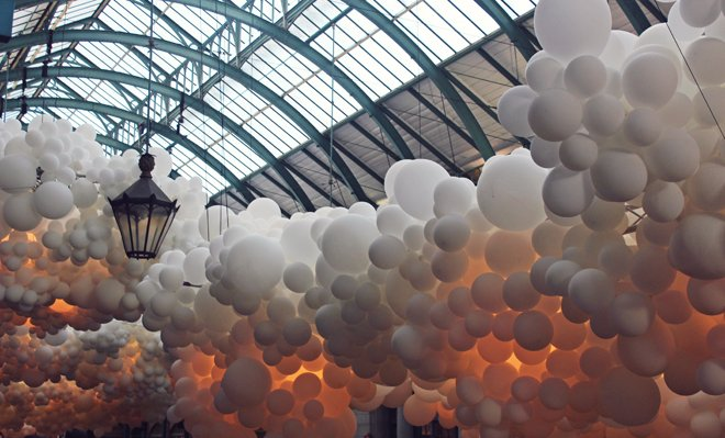 The moodily lit balloons give an atmospheric feel to domed ceiling of London's Convent Gardens Market Hall.