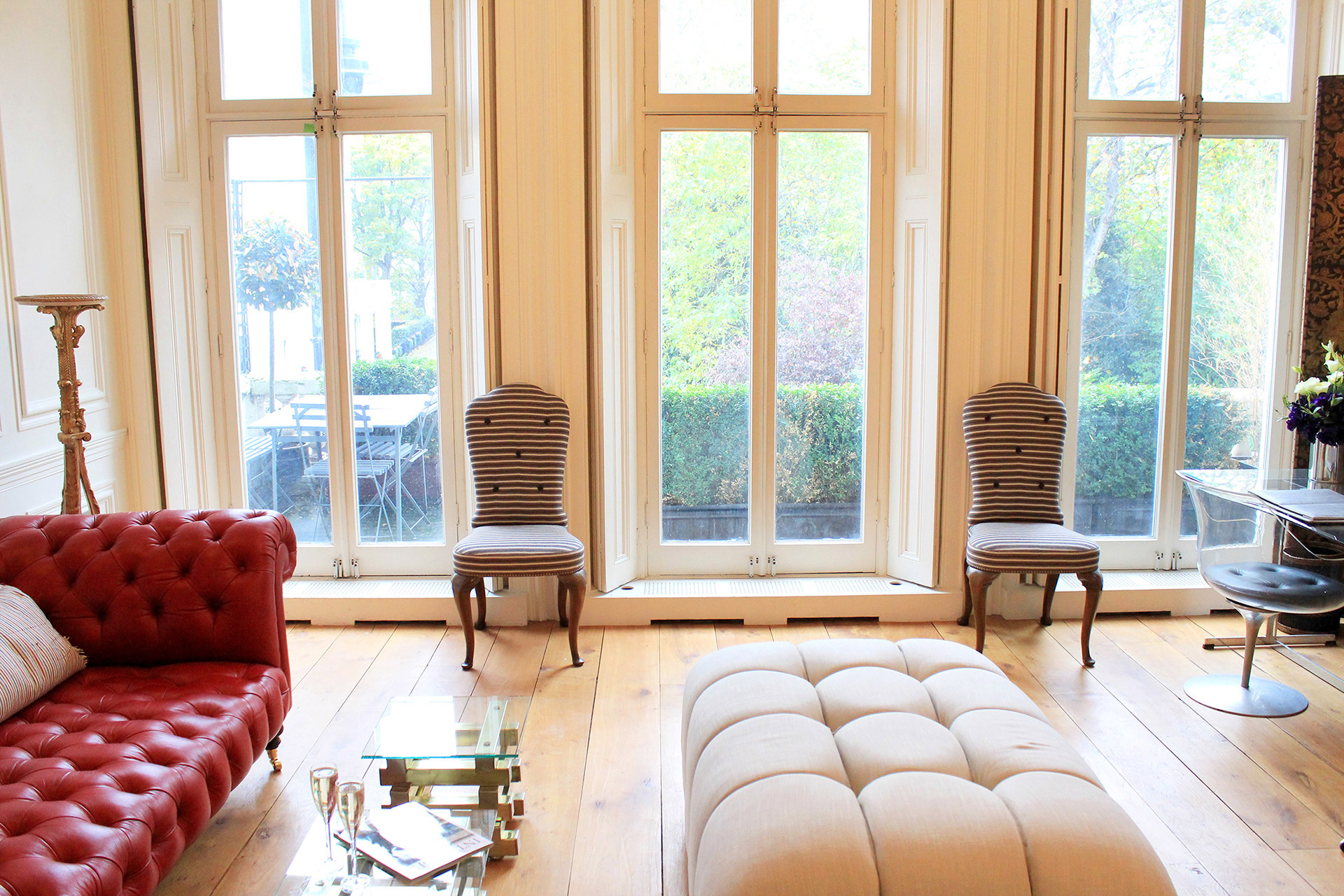 Large French Doors Open To Terrace And Balcony With Table