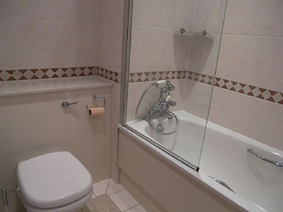 First en suite with shower over tub, sink and toilet