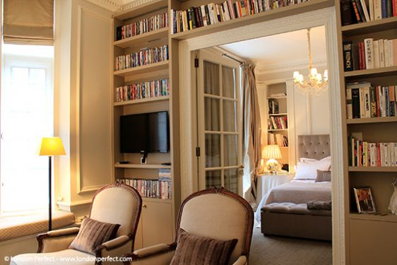 Bookshelves line the wall with entry to the bedroom