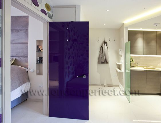 Aubergine coloured door leads to the bedroom