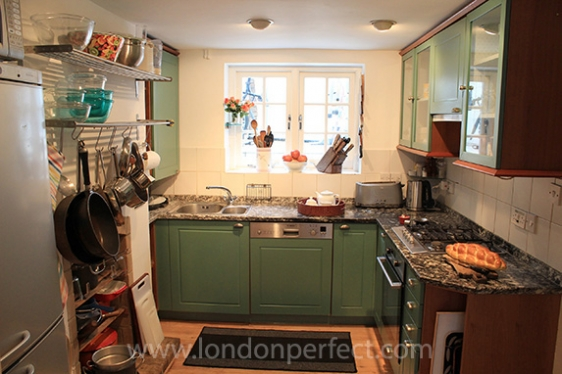 London kitchen with marble counters and green cabinets