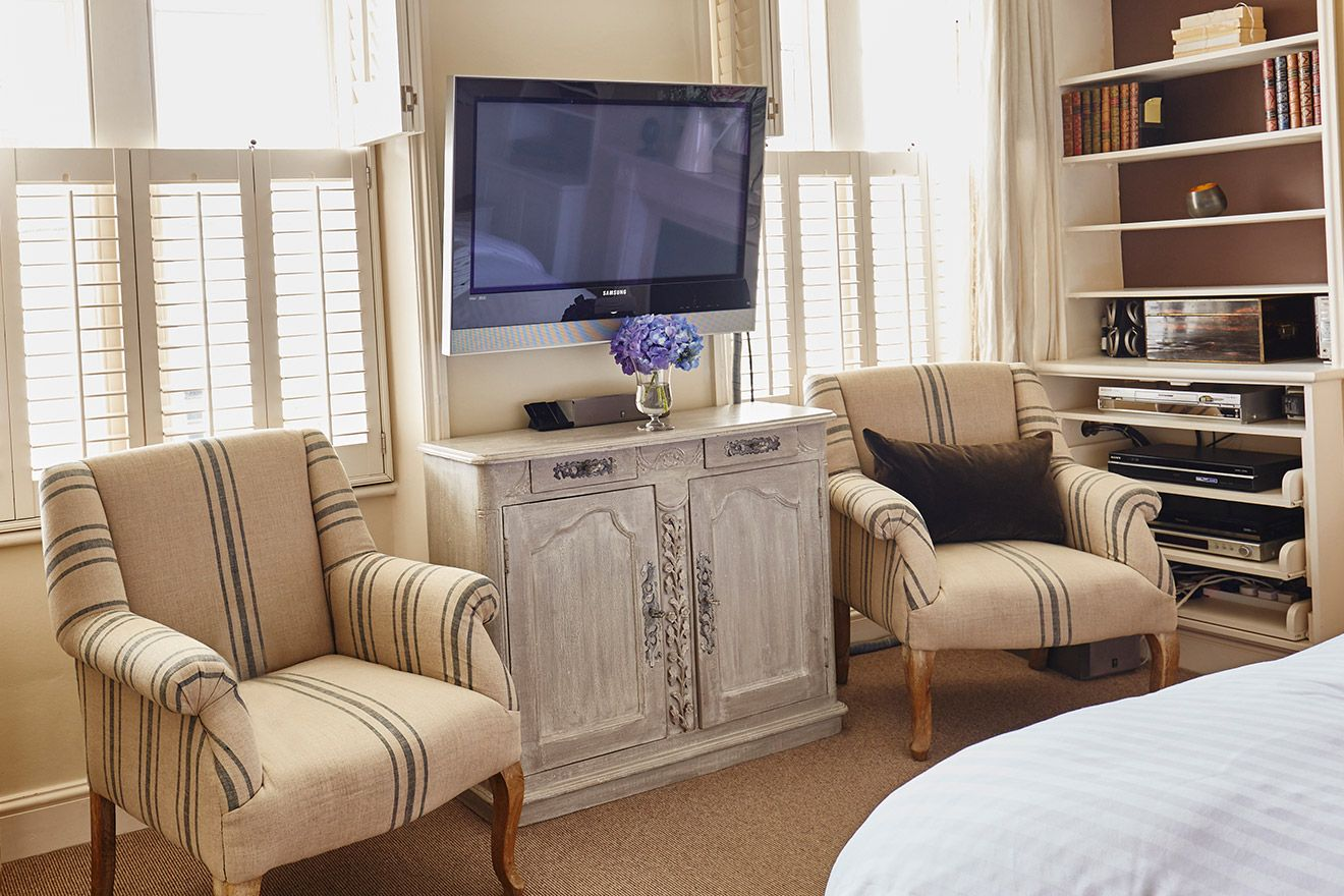 Flat screen TV and two armchairs in the first bedroom of the Victoria rental