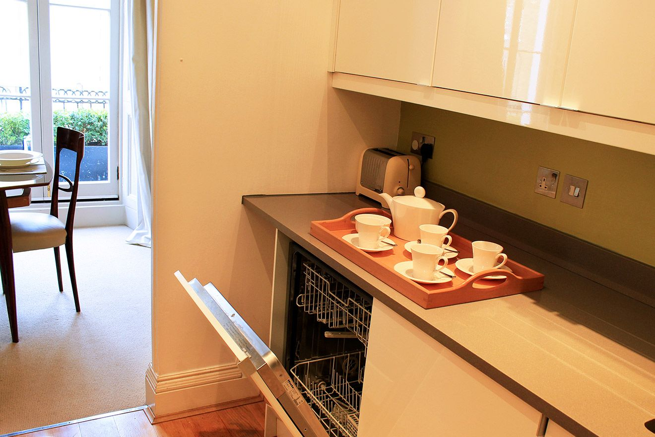 Kitchen is conveniently located just off dining room in the Belgravia vacation rental offered by London Perfect
