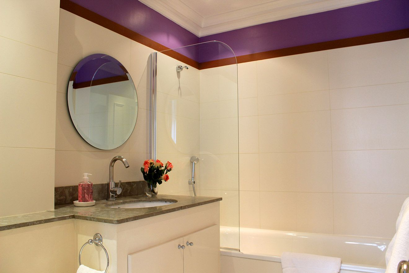 En suite bathroom with shower- bath combo, toilet and sink