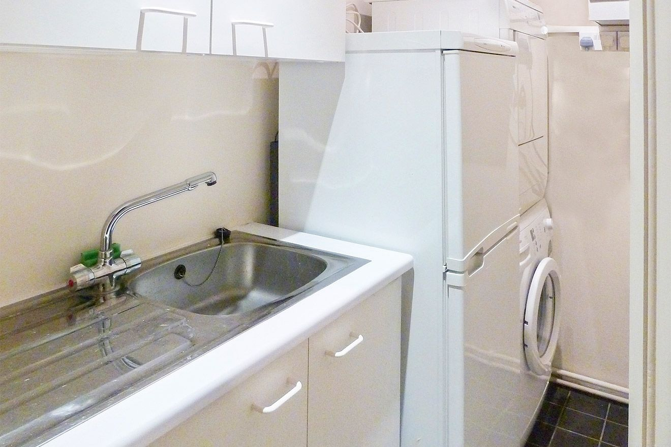 Utility room with washer, dryer and full size refrigerator
