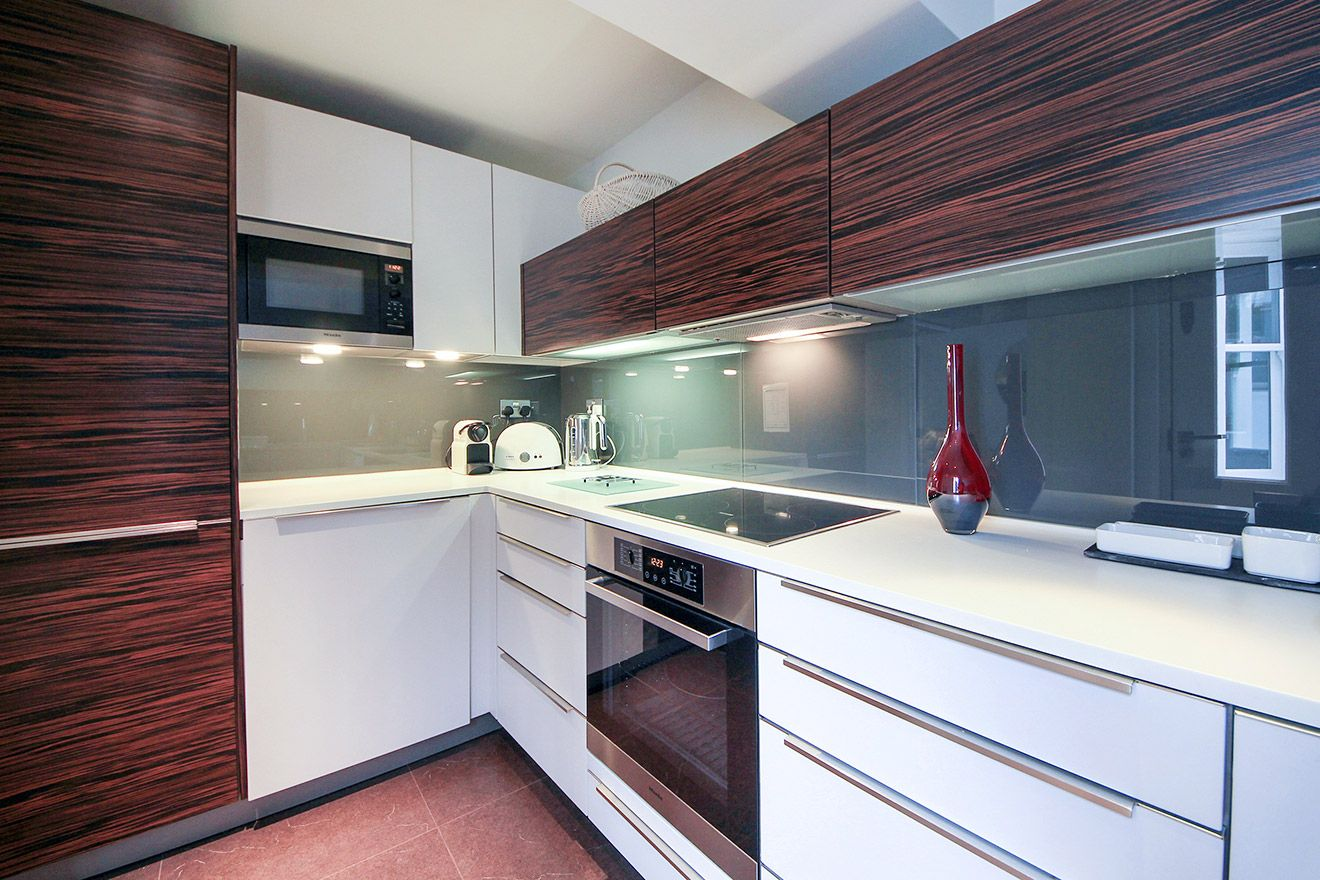 Modern kitchen with teak cabinets in the Gladstone vacation rental offered by London Perfect