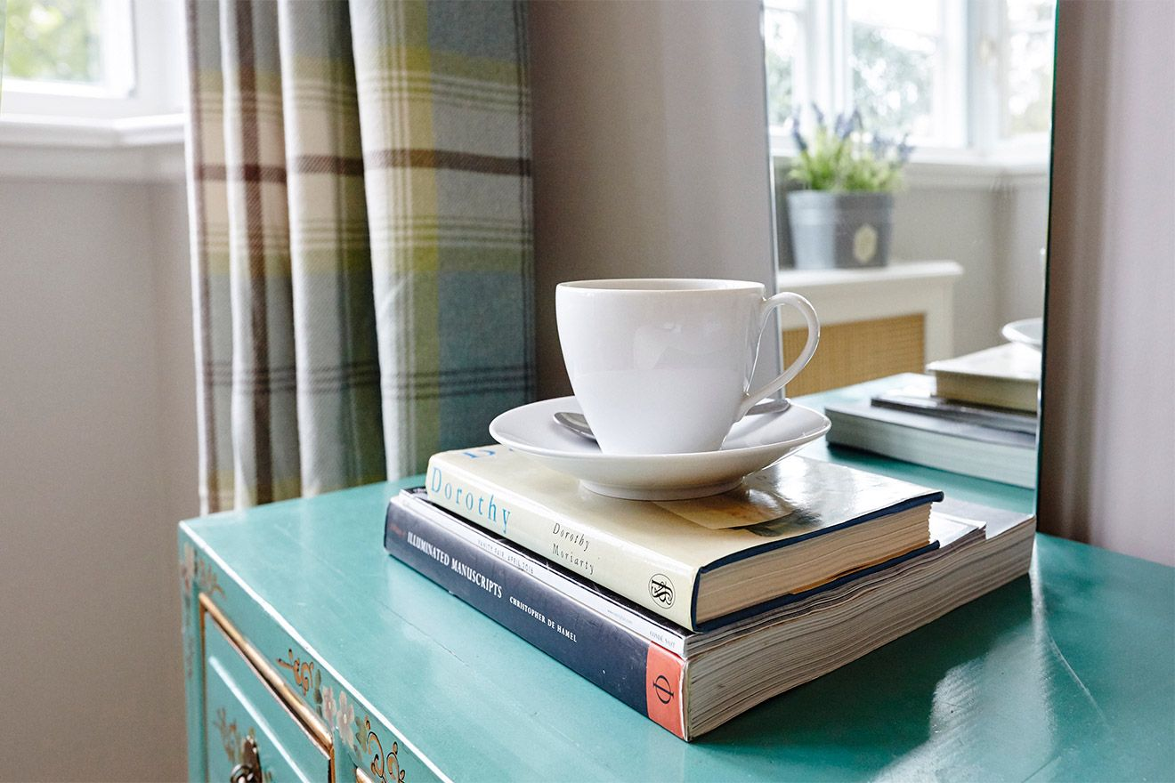 Books and coffee cup in the MacDonald vacation rental offered by London Perfect