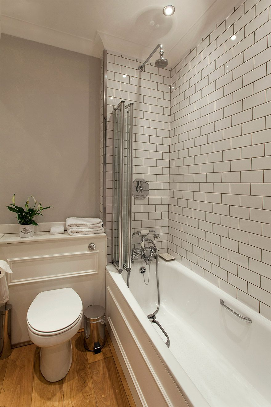 Soaking tub with fixed and flexible shower heads in the Austen vacation rental offered by London Perfect