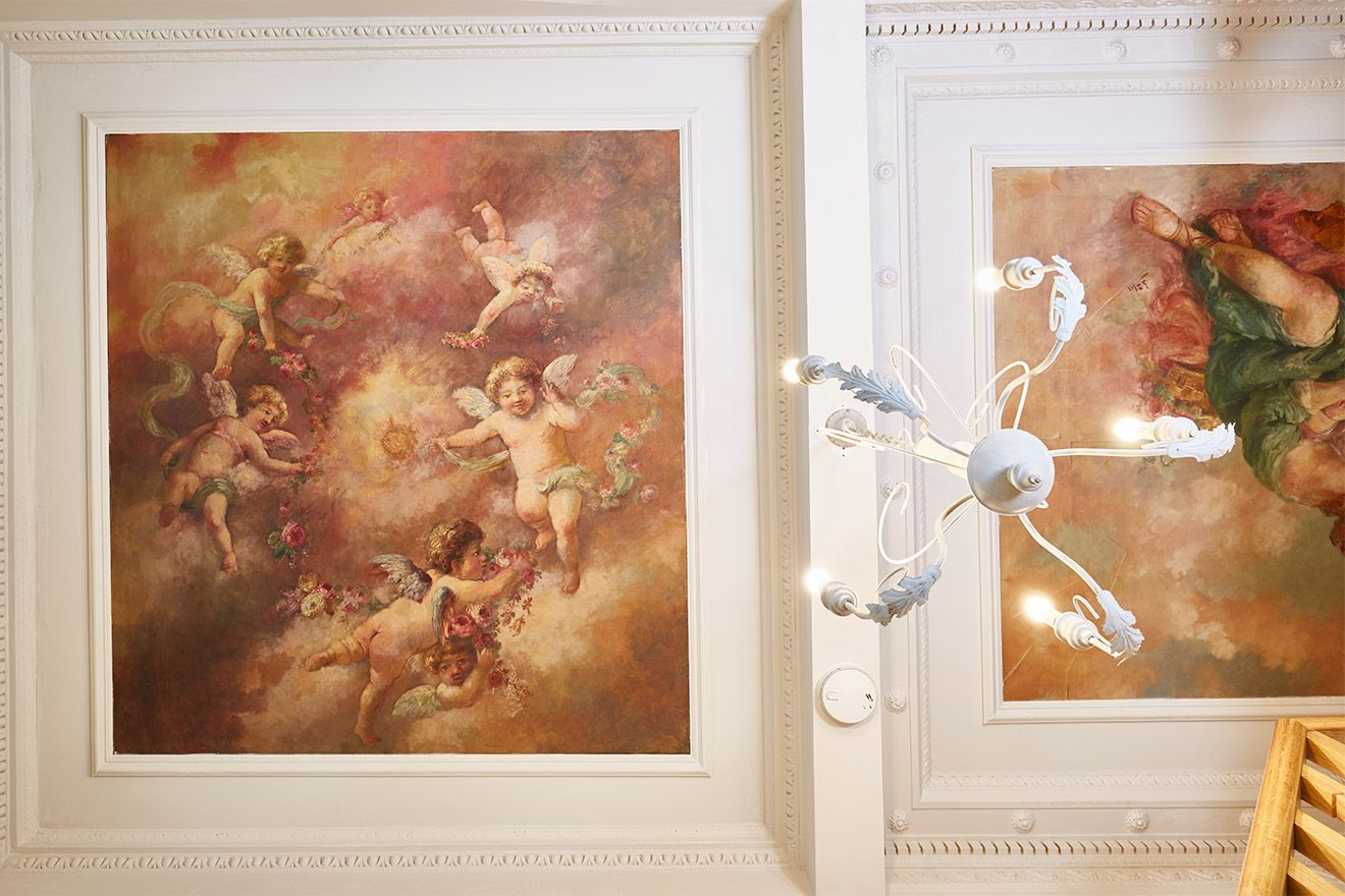 Paintings decorate the walls and ceiling