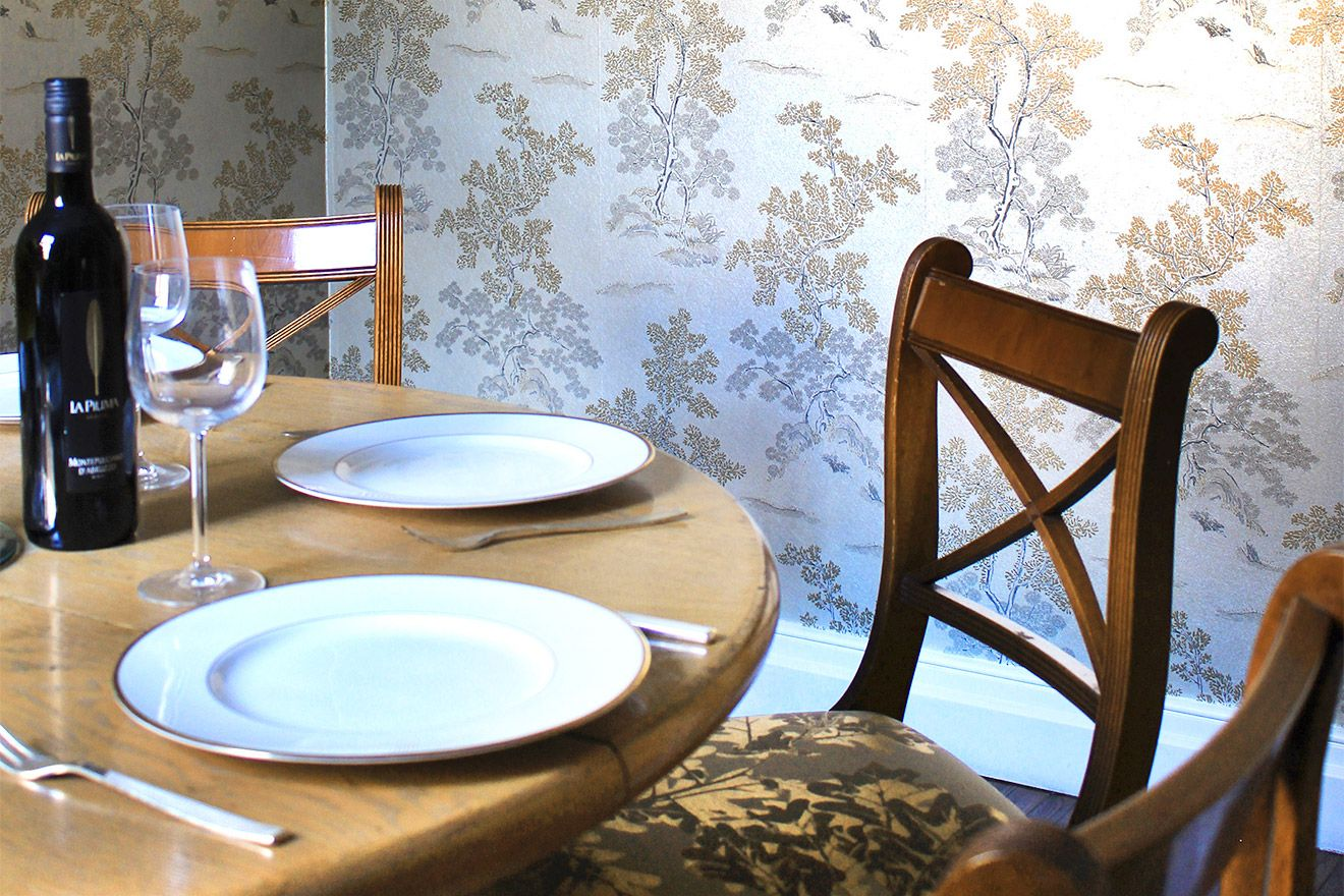 Rich woods and delicate wallpaper in the dining room of the Christchurch vacation rental