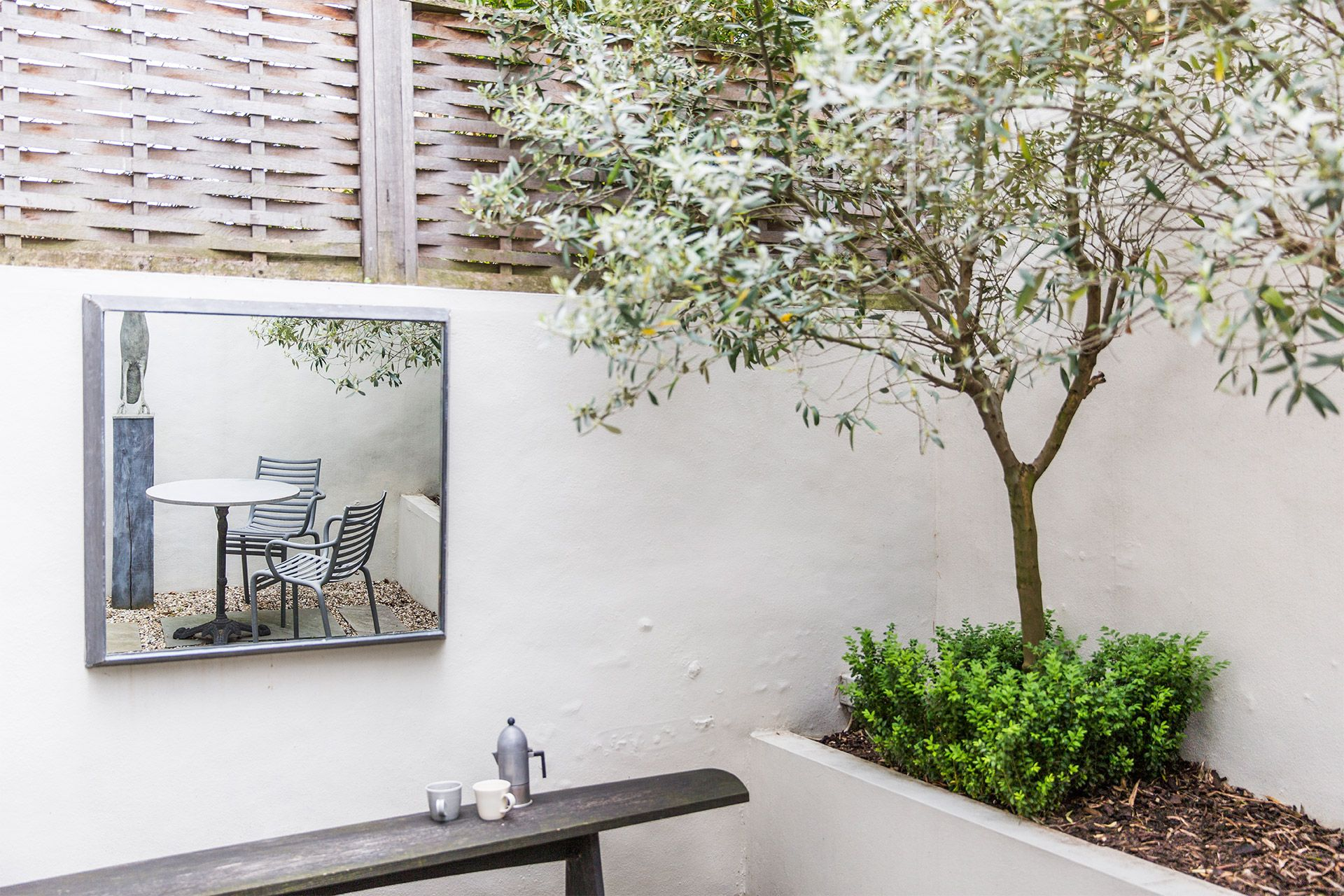Back patio with pretty olive trees in The Walton vacation rental offered by London Perfect